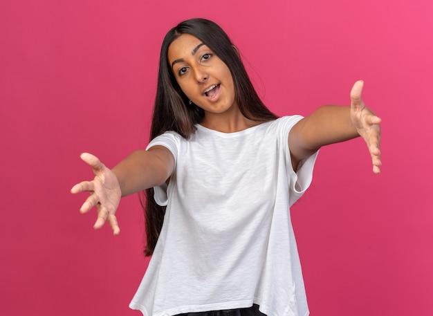 Jeune fille en t-shirt blanc regardant la caméra souriant joyeusement faisant un geste de bienvenue large ouvrant les mains debout sur fond rose