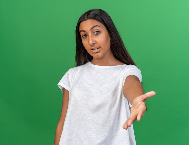 Jeune Fille En T-shirt Blanc Regardant La Caméra Souriante Amicale Faisant Venir Ici Un Geste Debout Sur Fond Vert Photo gratuit