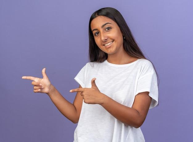 Jeune fille en t-shirt blanc regardant la caméra avec un sourire sur un visage heureux pointant avec l'index sur le côté debout sur fond bleu