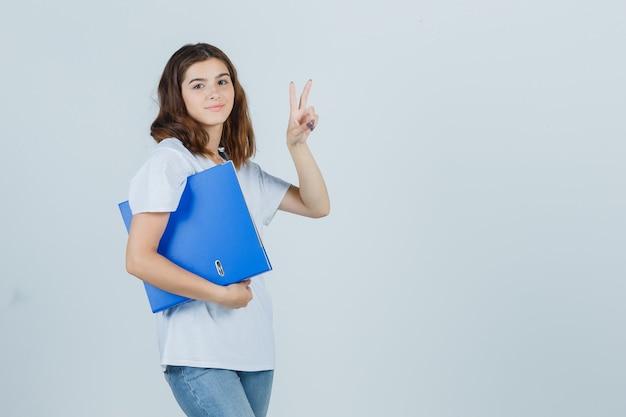 Jeune fille en t-shirt blanc tenant le dossier, montrant le geste de la victoire et l'air confiant, vue de face.