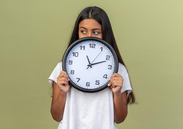 Jeune fille en t-shirt blanc tenant une horloge murale à côté avec un visage sérieux debout sur fond vert