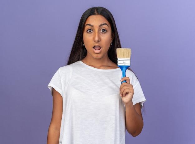 Jeune fille en t-shirt blanc tenant un pinceau regardant la caméra étonné et surpris debout sur bleu