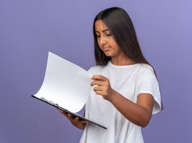 Jeune fille en t-shirt blanc tenant un presse-papiers avec des pages blanches le regardant avec un visage sérieux