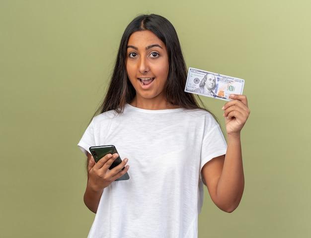 Jeune fille en t-shirt blanc tenant un smartphone montrant de l'argent en regardant la caméra heureuse et surprise