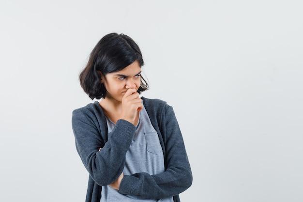 Jeune fille en t-shirt gris clair et sweat à capuche zippé gris foncé debout en pensant poser et à la pensif,
