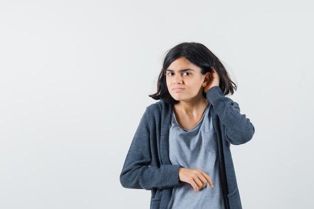 Jeune fille en t-shirt gris clair et sweat à capuche zippé gris foncé levant la main près de l'oreille comme essayant d'entendre quelque chose et à la recherche concentrée