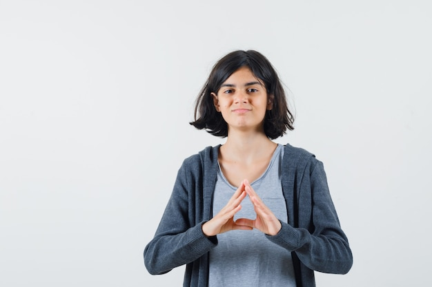 Jeune fille en t-shirt gris clair et sweat à capuche zippé gris foncé montrant la forme du triangle avec les mains et à la jolie