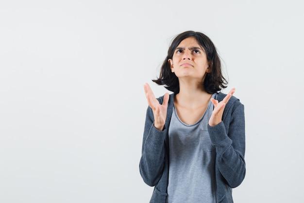 Jeune fille en t-shirt gris clair et sweat à capuche zippé gris foncé qui s'étend de la main comme essayant de tenir quelque chose et regardant au-dessus et à la surprise