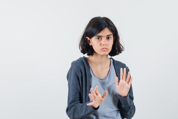 Jeune fille en t-shirt gris clair et sweat à capuche zippé gris foncé qui s'étend des mains comme l'arrêt de quelque chose et à la sérieuse,