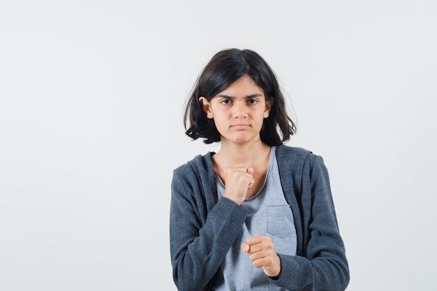 Jeune fille en t-shirt gris clair et sweat à capuche zippé gris foncé serrant le poing tout en se pointant et à la sérieuse,