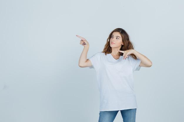 Jeune fille en t-shirt, jeans pointant vers le coin supérieur gauche et à la vue de face, confiant.