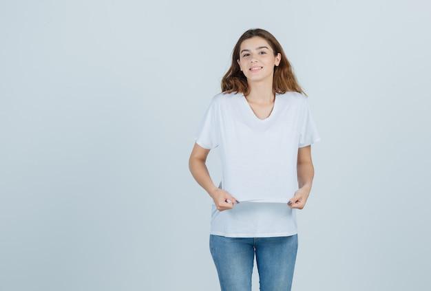 Jeune fille en t-shirt, jeans regardant la caméra tout en tenant le t-shirt et à la jolie vue de face.