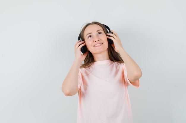 Jeune fille en t-shirt rose, appréciant la musique avec des écouteurs et à la joyeuse vue de face.