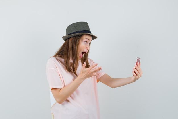 Jeune fille en t-shirt rose, chapeau faisant appel vidéo et regardant étonné, vue de face.