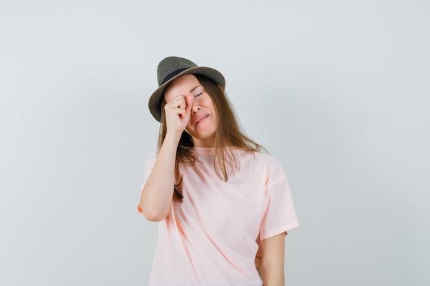 Jeune fille en t-shirt rose, chapeau frottant les yeux en pleurant et à la vue offensée, de face.