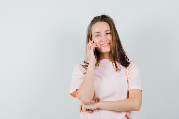 Jeune fille en t-shirt rose parlant au téléphone mobile et à la jolly, vue de face