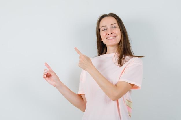 Jeune fille en t-shirt rose pointant vers le coin supérieur gauche et à la joyeuse vue de face.