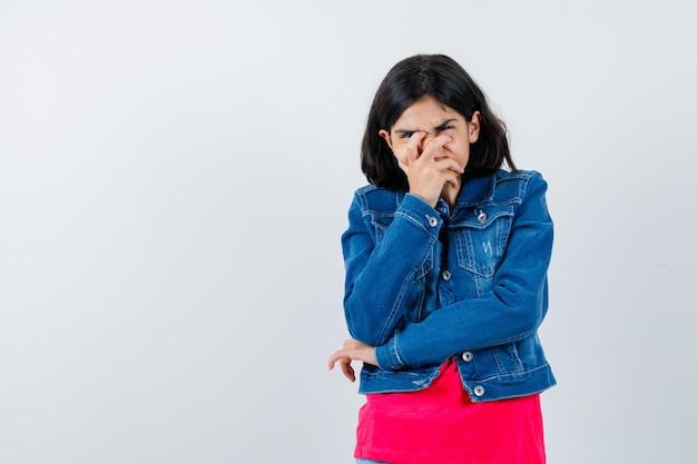 Jeune fille en t-shirt rouge et veste en jean couvrant la bouche avec la main et l'air harcelé, vue de face.