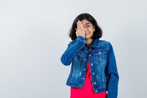 Jeune fille en t-shirt rouge et veste en jean couvrant les yeux avec la main et l'air heureux, vue de face.