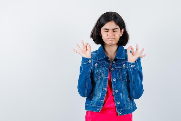 Jeune fille en t-shirt rouge et veste en jean debout dans une pose de méditation et l'air calme, vue de face.