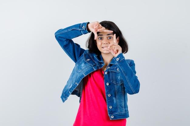 Jeune fille en t-shirt rouge et veste en jean montrant le geste du cadre avec les deux mains et l'air sérieux, vue de face.