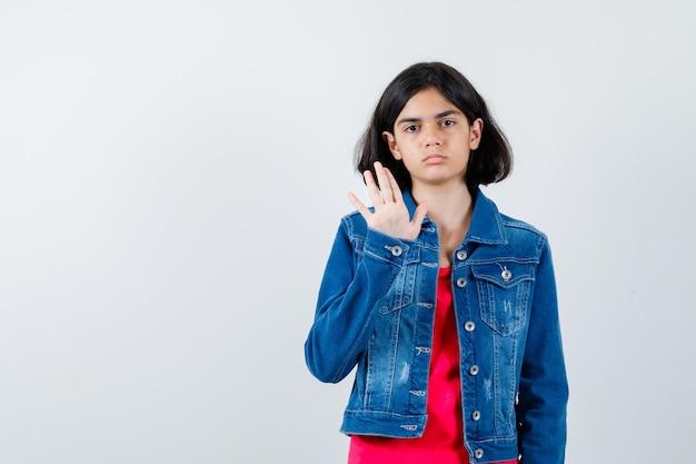 Jeune fille en t-shirt rouge et veste en jean montrant un panneau d'arrêt et ayant l'air sérieux