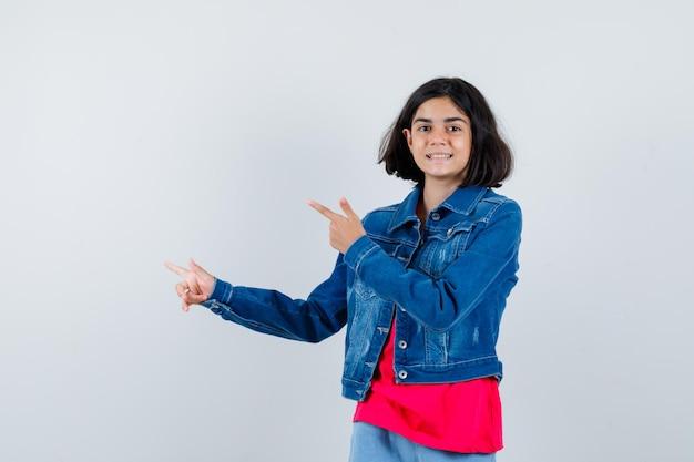 Jeune fille en t-shirt rouge et veste en jean pointant vers la gauche avec l'index et l'air heureux, vue de face.