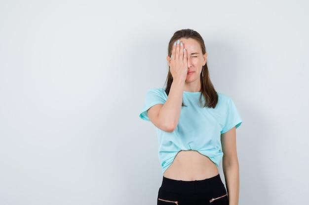Jeune fille en t-shirt turquoise, pantalon couvrant le visage avec la paume et l'air confus, vue de face.