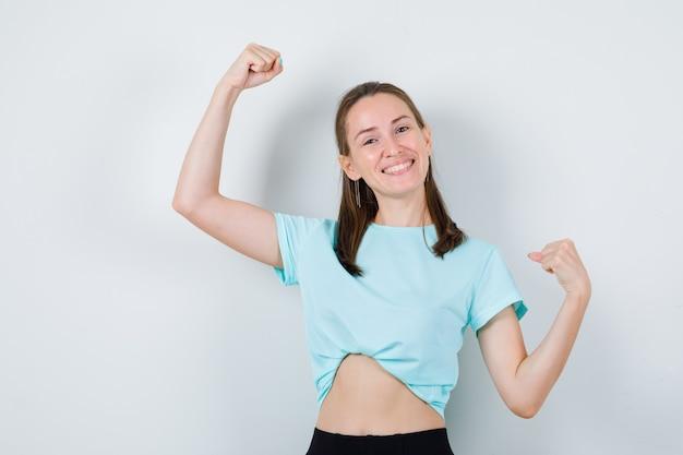 Jeune fille en t-shirt turquoise, pantalon montrant le geste du vainqueur et l'air joyeux, vue de face.