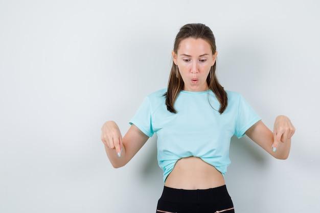 Jeune fille en t-shirt turquoise, pantalon pointant vers le bas avec les doigts et l'air choqué, vue de face.