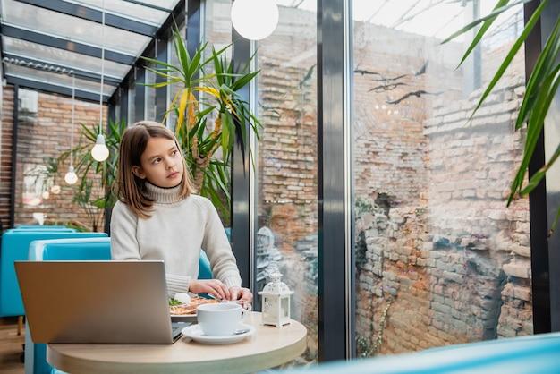 La jeune fille à la table dans un café avec un ordinateur portable regarde par la fenêtre.