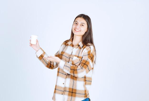 Jeune fille avec une tasse de thé se sentant heureuse sur un mur blanc.