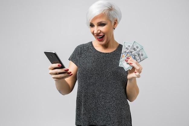 Jeune fille avec un téléphone et un fan de dollars dans ses mains se dresse isolé sur un fond clair