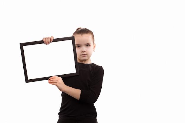 Jeune fille tenant une assiette vide sur un fond blanc