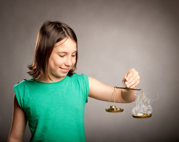 Jeune fille tenant une balance de la justice avec de l'argent et de la fumée