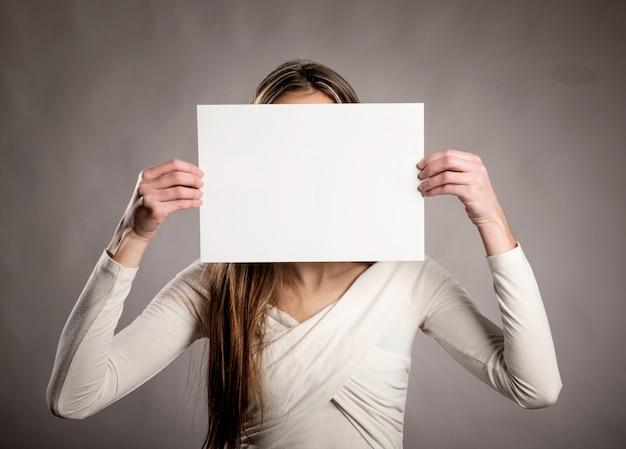 Jeune fille tenant une bannière vide devant son visage