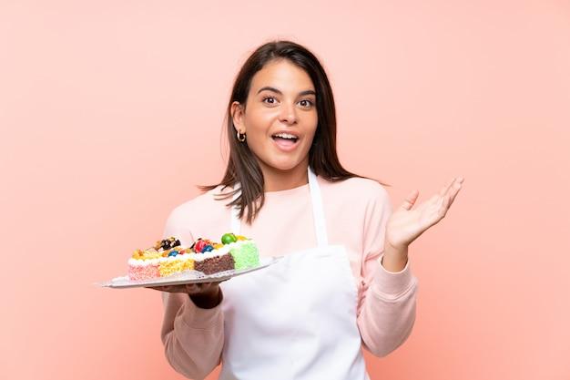 Jeune fille tenant beaucoup de mini gâteaux différents sur un mur isolé avec une expression faciale choquée