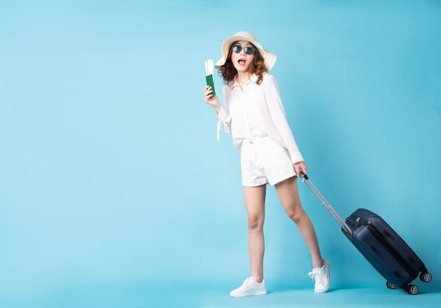 Jeune fille tenant le billet d'avion se préparant pour le prochain voyage avec une expression joyeuse