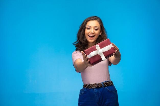 Jeune fille tenant une boîte-cadeau et souriant.
