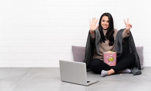 Jeune fille tenant un bol de pop-corn et montrant un film dans un ordinateur portable en comptant sept avec les doigts