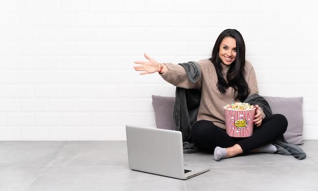 Jeune fille tenant un bol de pop-corn et montrant un film dans un ordinateur portable présentant et invitant à venir avec la main