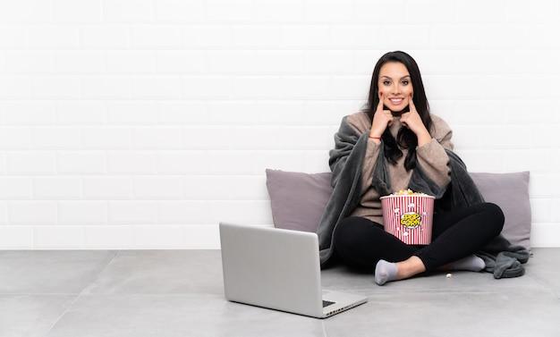 Jeune fille tenant un bol de pop-corn et montrant un film dans un ordinateur portable souriant avec une expression heureuse et heureuse
