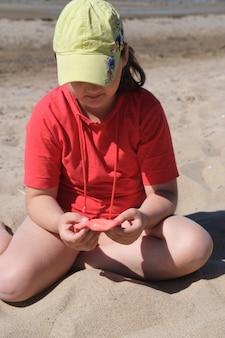Jeune fille tenant une boue rouge vif dans ses mains concept d'enfance créativité éducation sélective