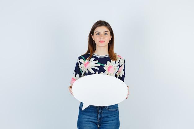 Jeune fille tenant une bulle de dialogue en blouse florale, un jean et l'air heureux, vue de face.