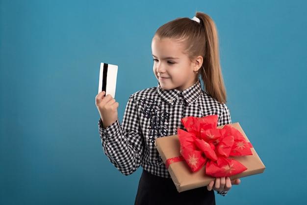 Jeune fille tenant un cadeau avec et une carte de crédit et souriant