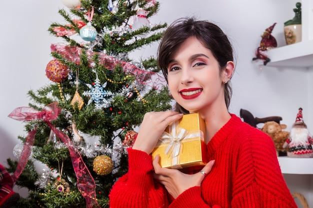 Jeune fille tenant un cadeau de noël