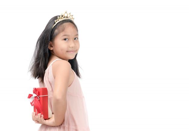 Jeune fille tenant un cadeau rouge derrière son dos isolé