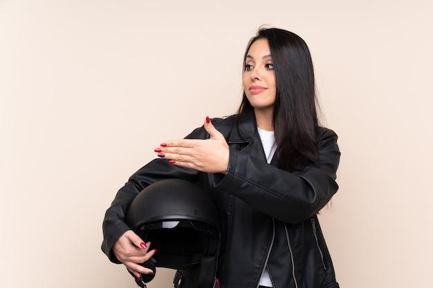 Jeune fille tenant un casque de moto sur le mur, tendant les mains sur le côté pour inviter à venir