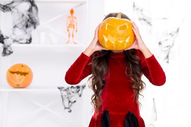 Jeune fille tenant une citrouille sculptée