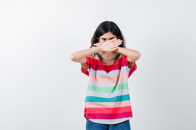 Jeune fille tenant deux bras croisés, ne faisant aucun signe en t-shirt à rayures colorées et ayant l'air sérieux. vue de face.